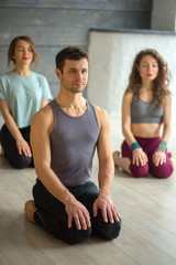 Young sportive male instructor practicing yoga with group of young women in studio over grey background. Training, Flexibility, Well-being Concept