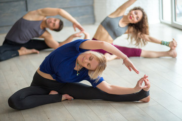 Yoga, pilates, healthy Activities, Training and lifestyle concept - group of sportive people stretching on the floor in well-lit studio over calm grey background.