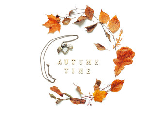 Autumn background - autumn leaves, bronze clock in form of the owl and Autumn time letters on the white background