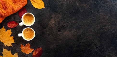 Top view of two cups of coffee around yellow leaves