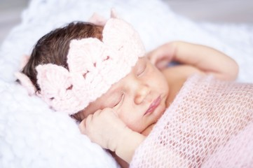 Sweet sleeping tiny newborn princess with a pink crown wrapped in a soft blanket. Cute newborn baby sleeping stock image.