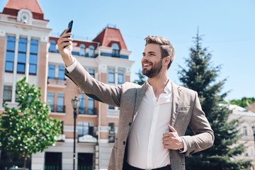 Handsome elegant young man taking a selfie in the city
