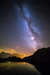 Milky Way and Starry Sky over Iconic Snowy Mont-Blanc Peaks Reflecting in Altitude Lake.