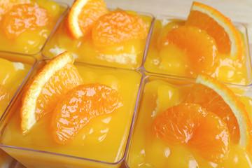 Fototapeta Many Vibrant Color Mandarin Orange Cakes in Glass Bowls Topped with Fresh Oranges