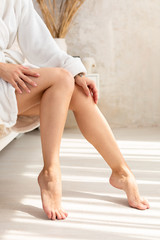 Close-up of legs of woman in white terry bathrobe on bed with ideal figure in light room.