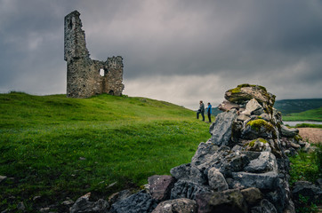 Haunted abbandoned ruined medieval castle tower during cloudy sky