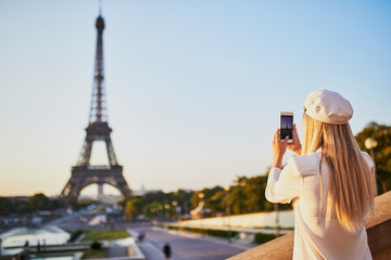 woman with long blond hair taking photo of the Eiffel tower