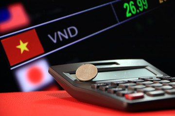 Two hundred Vietnam Dong coin on reverse (VND) on black calculator and red floor with digital board of currency exchange money background,