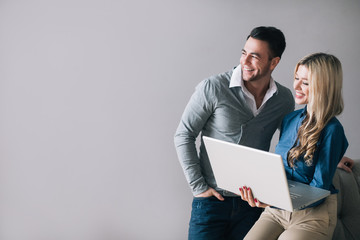 Smiling man and woman with a laptop