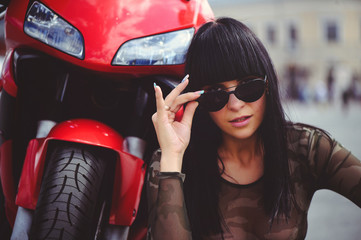 happy woman biker sitting near motorcycle and happy, close-up brunette with red bike