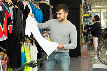 Young man choosing sport shirt in shop