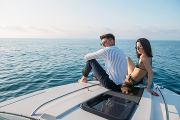 Recess Fitting Water Motor sports Attractive caucasian couple sunbathing on a motor boat enjoying marine trip along sea coast. Perfect celebration of a honeymoon with great beautiful seascapes with copyspace for message