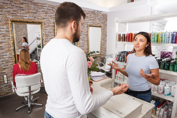 Male client talking with female assistant about  services at beauty salon