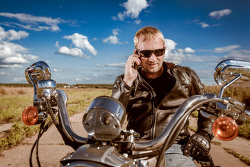 Fototapete - Biker talking on a smartphone.
