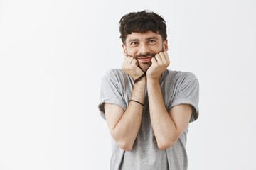 So cute my male heart melting. Portrait of touched happy and pleased good-looking funny guy with beard holding palms on cheeks leaning on hands and smiling with affection and amusement