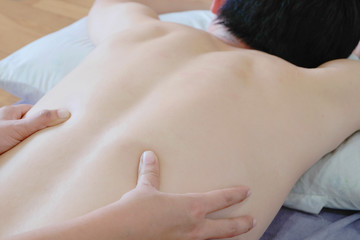 Massage therapist massaging lower back region of a male athlete.