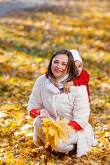 Cute,happy, white boy in red shirt smiling and hugging with his mom among yellow leaves. Little child having fun with mother in autumn park. Concept of friendship between son and parents, happy family