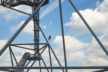 People rappel from top of the tetrahedron, steel tube structural sculpture which foam as pyramid or tetrahedron is located on the hill top of the mine dump Halde Beckstraße in Bottrop, Germany.