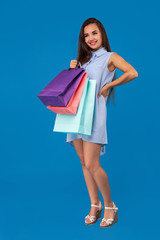 Photo of beautiful young woman with colorful shopping bags on the wonderful blue background