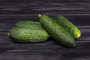 Four cucumbers on wood. Black wooden table background.