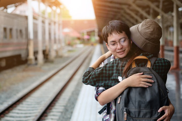 Couple traveller hug for good bye at train station with a traveler.