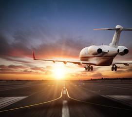 Poster Avion à Moteur Private jet plane landing on runway in beautiful sunset light.