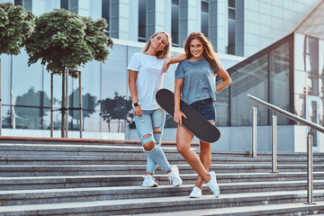 Two beautiful hipster girls standing on steps with skateboard on a background of the skyscraper.