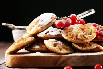 Pancakes or puffertjes with berries and maple syrup on rustic table