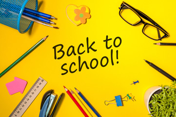 Back to school - Message at yellow background with many little color letters and school supplies. Education concept, 1 september time