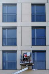 Fensterputzer putzt Fenster  / Ein Fensterputzer steht auf einer Hebebühne und putzt die Fenster eines Hochhauses.