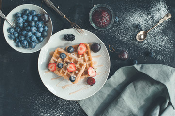Waffles with berries on black background, top view flat lay