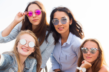 A close-up selfie of the four beautiful bridesmaids in colorful sunglasses on the background of the sky