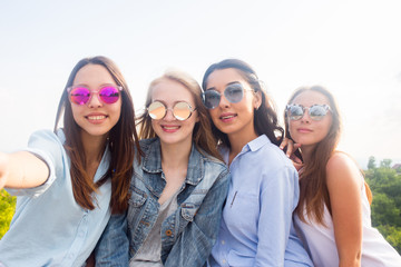 Four smiling attractive women doing selfie outdoor