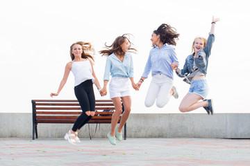 Four beautiful crazy joyful girlfriends jumping and having fun in park
