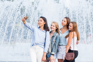 Four young beautiful women smile and take selfies