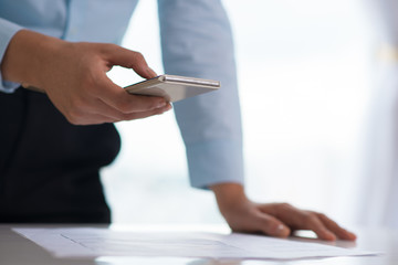 Closeup of person using smartphone and standing at desk. Digital gadget and document. Technology and business concept. Cropped view.