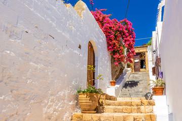 Beautiful Greek street with summer flowers in Lindos village. Rhodes island. Greece.