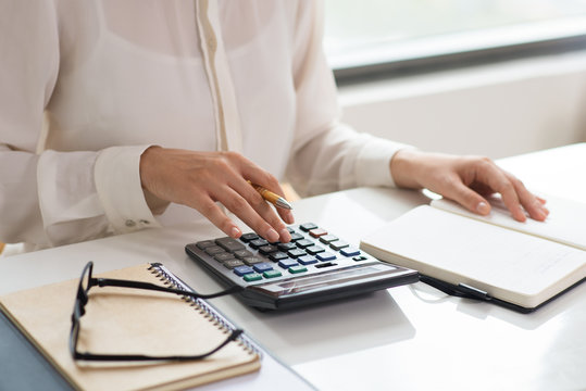 Closeup of woman calculating expenses. Notebooks, glasses and calculator lying on desk. Finance concept. Cropped view.