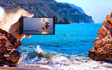 High contrast vibrant image of famous blue emerald sea bay near the birthplace of Aphrodite of Cyprus in summer 2018 with human hand and smart phone displaying moon eclipse