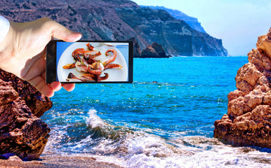 High contrast vibrant image of famous blue emerald sea bay near the birthplace of Aphrodite of Cyprus in summer 2018 with human hand and smart phone displaying sea food