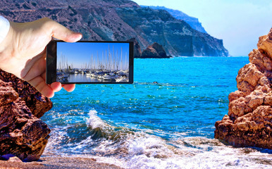 High contrast vibrant image of famous blue emerald sea bay near the birthplace of Aphrodite of Cyprus in summer 2018 with human hand and smart phone displaying boats
