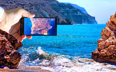 High contrast vibrant image of famous blue emerald sea bay near the birthplace of Aphrodite of Cyprus in summer 2018 with human hand and smart phone displaying air map of the country