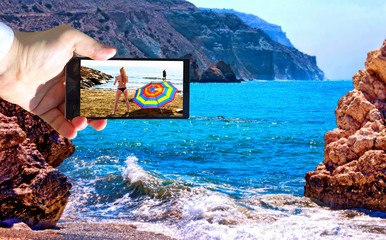High contrast vibrant image of famous blue emerald sea bay near the birthplace of Aphrodite of Cyprus in summer 2018 with human hand and smart phone  dispaying bikini girls