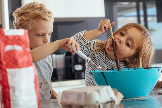 Children mixing batter for baking