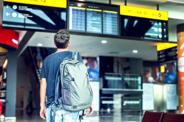 A young male traveler with a backpack looks at the information board at the airport. Getting information about the flight.