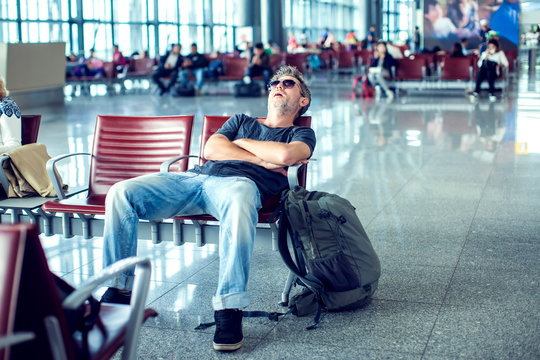 Man sleeping while sitting in airport terminal and waiting for flight departure
