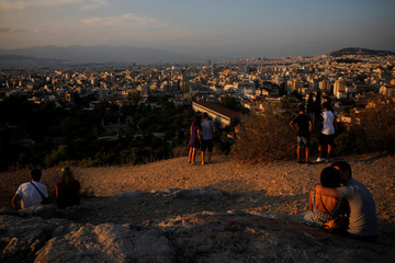 Tourists visit the Areios Pagos hill at the archaeological site of the Acropolis in Athens