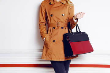 Wall Mural - Trendy woman with black and red bag in hand. Autumn outfit