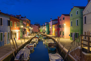 Colorful houses at night in Burano, Venice Italy. Night lights on the beautiful Burano island. Venice, Italy. Colourfully painted houses facade on Burano island in evening, province of Venice, Italy