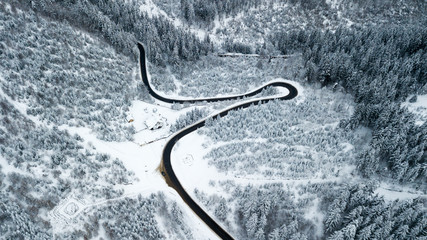 Foto auf AluDibond Grau Aerial view of a road crossing through a frozen forest during a cold winter day in Romania